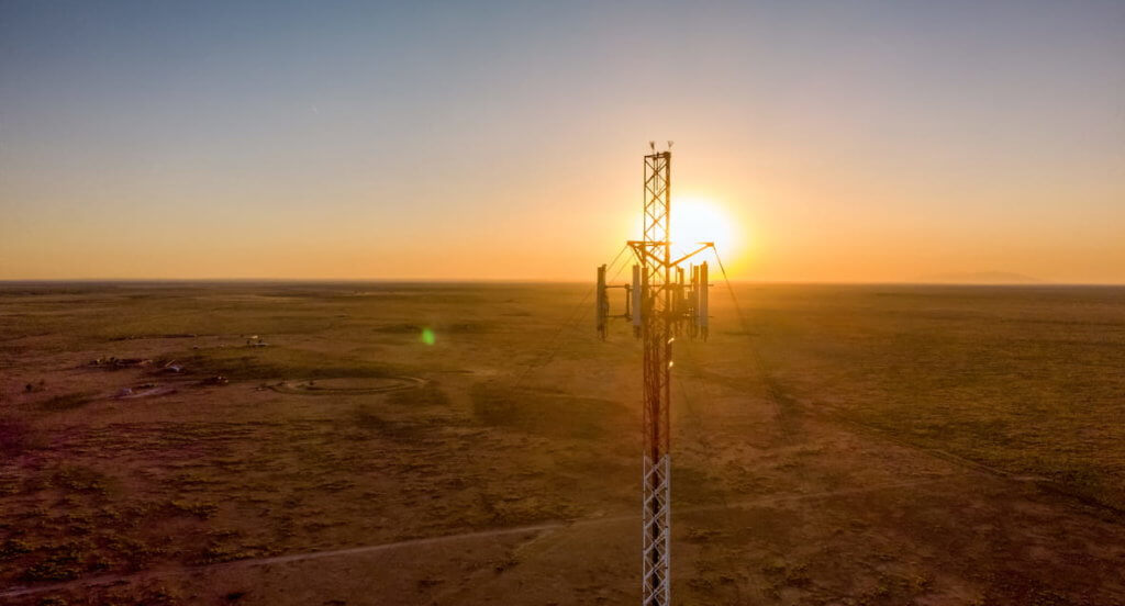Cellular communications tower for mobile phone and video data transmission, at sunset.