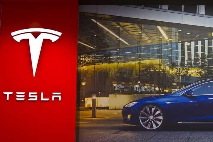 A blue Tesla EV in a showroom.