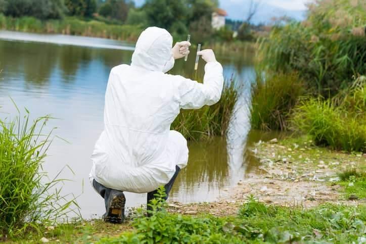 Scientific worker taking examples of water.