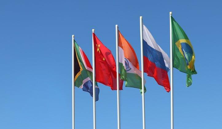 BRICS flags waving against the clear blue sky
