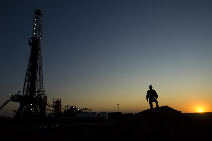 A mining worker stands in front of a drilling platform in the Australian desert