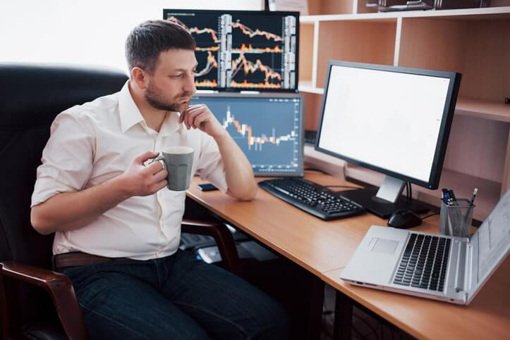 A trader sitting in office at table, working on computer with many monitors.